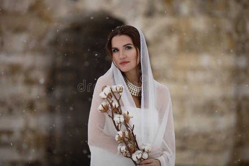 Novia joven en una bufanda que se coloca en el frío y que sostiene la flor del algodón foto de archivo libre de regalías