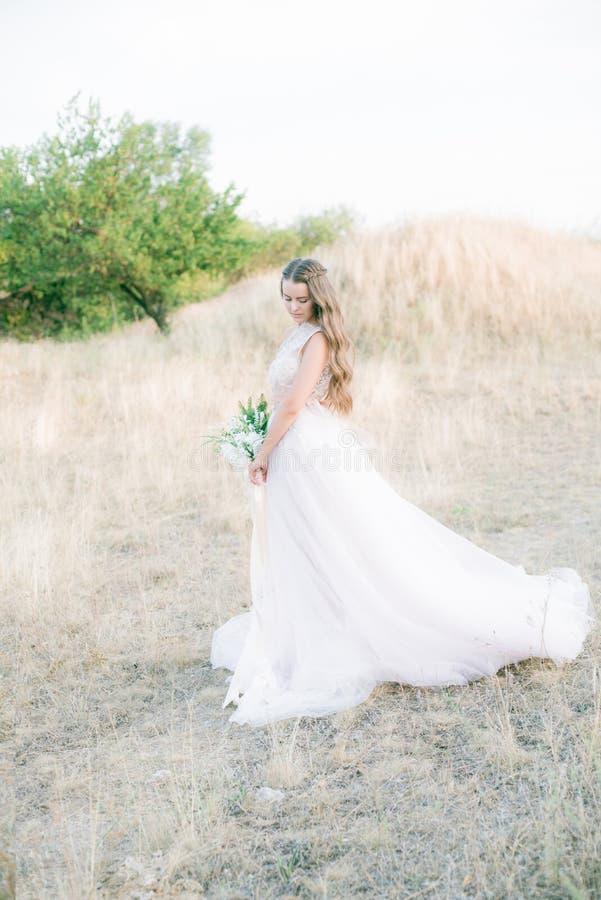 Novia joven hermosa con el pelo rizado rubio largo en un vestido blanco largo en el campo del verano fotografía de archivo