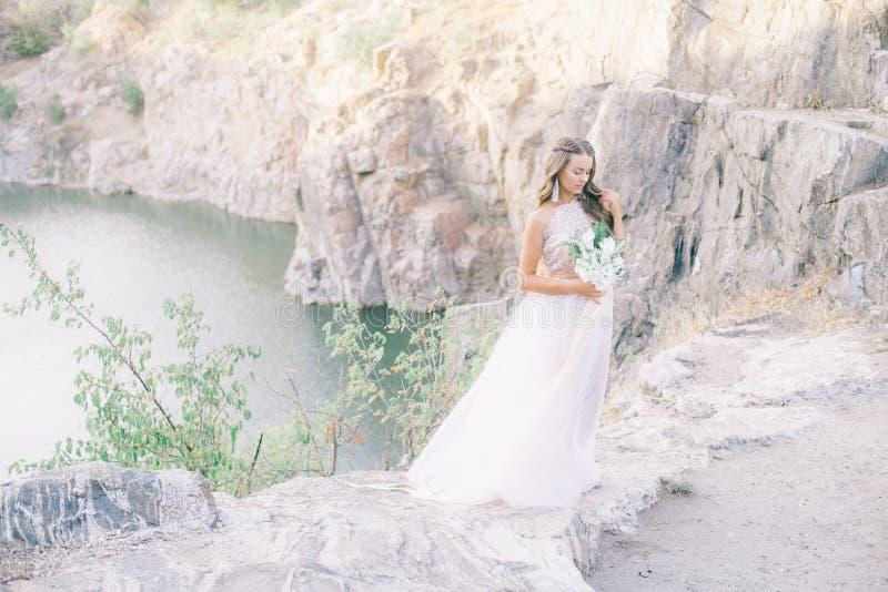 Novia joven hermosa con el pelo rizado rubio largo en un vestido blanco largo en el campo del verano foto de archivo libre de regalías