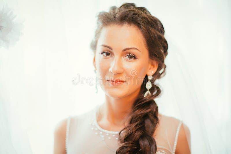 Novia joven hermosa con maquillaje de la boda y peinado en el dormitorio, preparación final de la mujer del recién casado para ca imagenes de archivo
