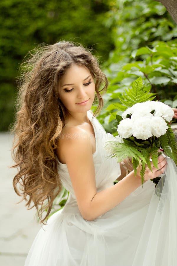 Novia joven hermosa con maquillaje largo del pelo ondulado y de la boda ho fotografía de archivo libre de regalías