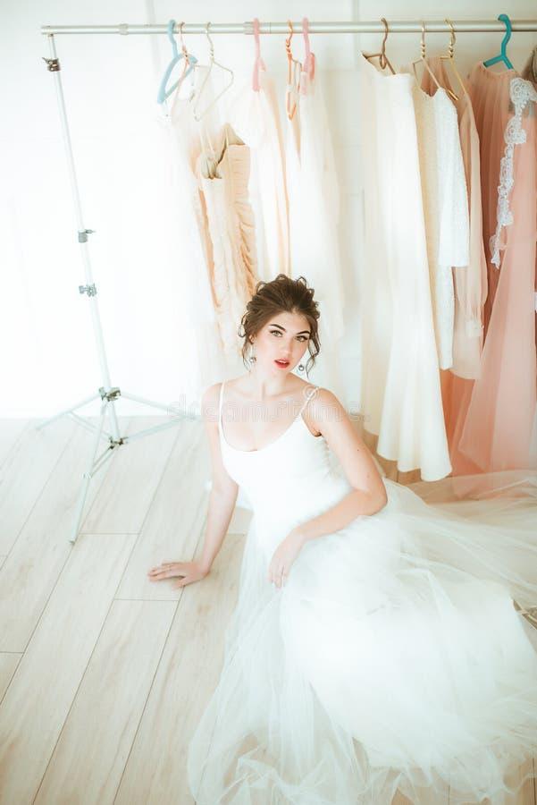 Novia joven hermosa en un vestido blanco en el sal?n en el fondo de otros vestidos fotos de archivo
