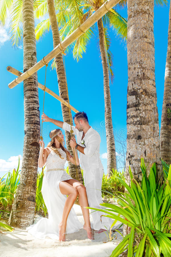 Novia joven hermosa en un vestido y un novio blancos debajo de una palma tr fotografía de archivo