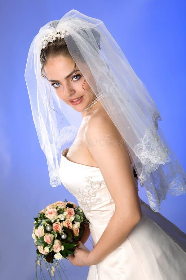 Novia joven hermosa en velo y vestido en fondo azul descubierto foto de archivo libre de regalías