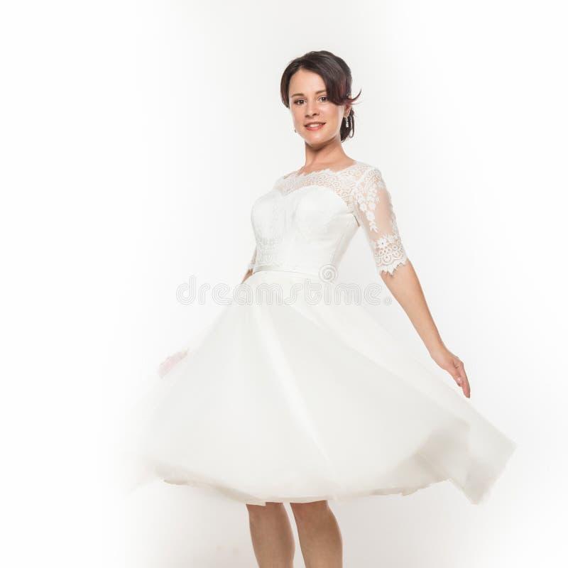 Novia joven hermosa en vestido blanco que vuela Vuelo blanco ligero del pa?o en el viento En un fondo blanco imagen de archivo