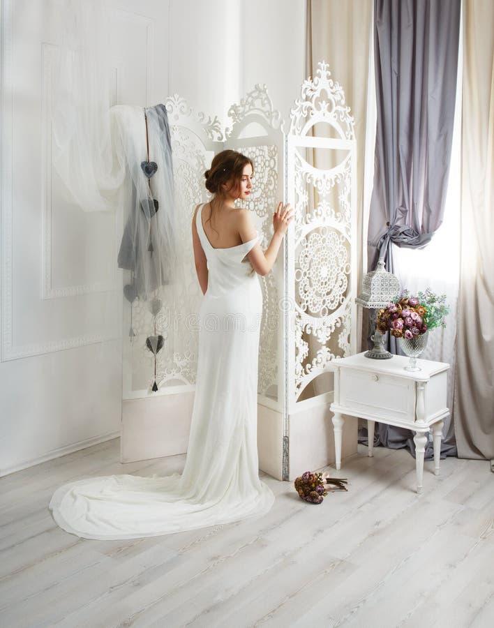 Novia joven hermosa en vestido de boda con el tren foto de archivo libre de regalías