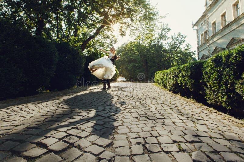 Novia joven hermosa y novio hermoso que bailan al aire libre cerca de o fotografía de archivo libre de regalías