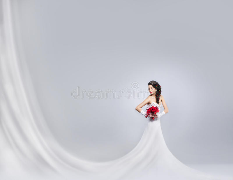 Novia joven y hermosa que se coloca con un ramo de la flor imagen de archivo