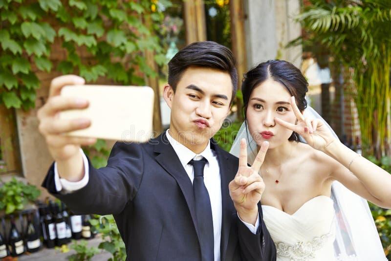 Novia joven y novio asiáticos que toman un selfie fotografía de archivo libre de regalías
