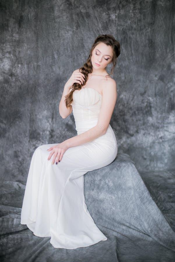 Novia linda joven con el peinado hermoso en un vestido blanco en un fondo gris fotografía de archivo libre de regalías