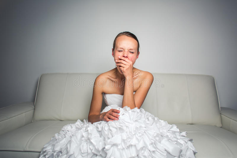 Novia magnífica cansada estupenda que se sienta en un sofá foto de archivo libre de regalías