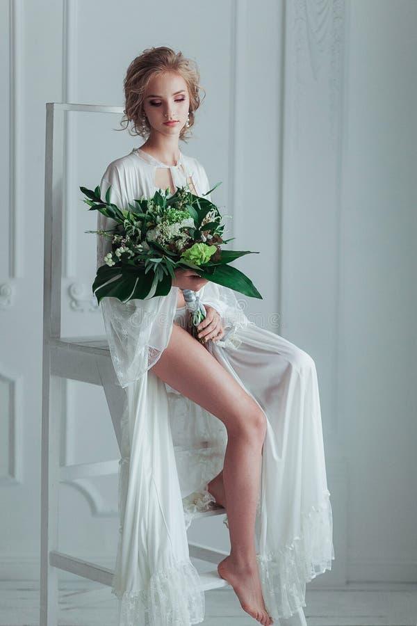 Novia magnífica con el ramo de la boda que se sienta en la escalera adornada fotografía de archivo