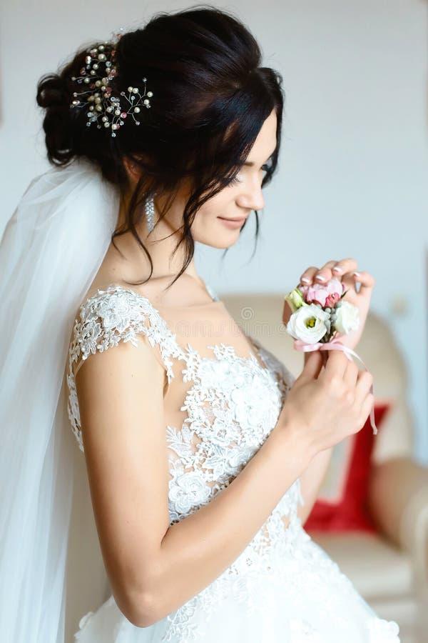Novia magnífica con el retrato del boutonniere cerca de la ventana gabinete de señora nupcial el día de boda mujer hermosa que co imagen de archivo libre de regalías