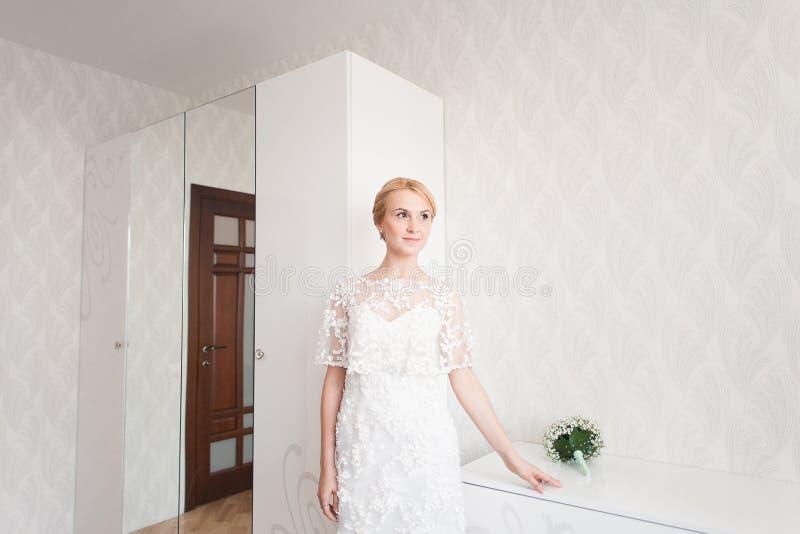 Novia magnífica con maquillaje del ramo de la boda y peinado en el vestido nupcial en casa que espera al novio fotografía de archivo libre de regalías