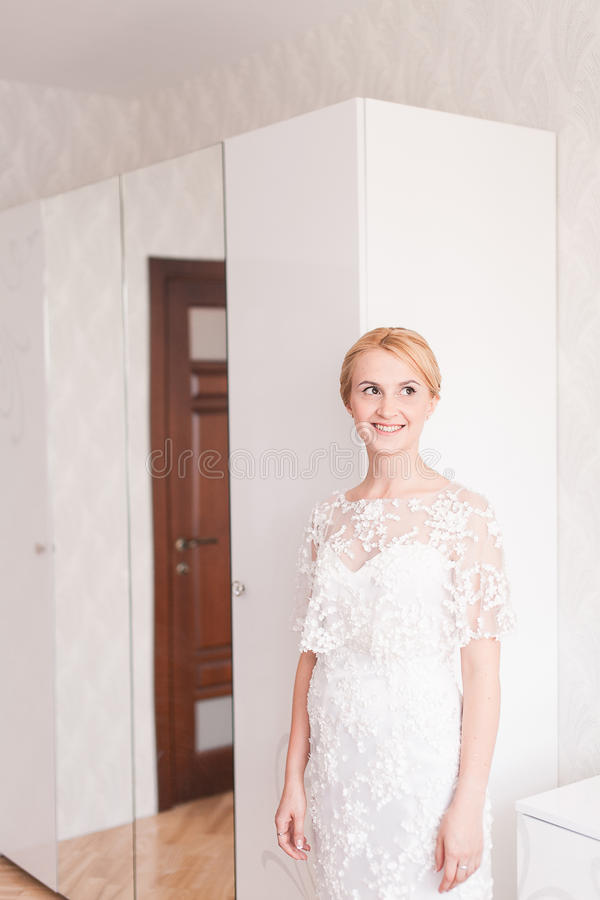 Novia magnífica con maquillaje del ramo de la boda y peinado en el vestido nupcial en casa que espera al novio fotos de archivo libres de regalías