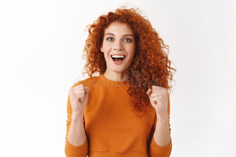Novia magnífica emocionada del pelirrojo que arraiga para el equipo preferido La muchacha rizada aprieta los puños motivados y am foto de archivo libre de regalías