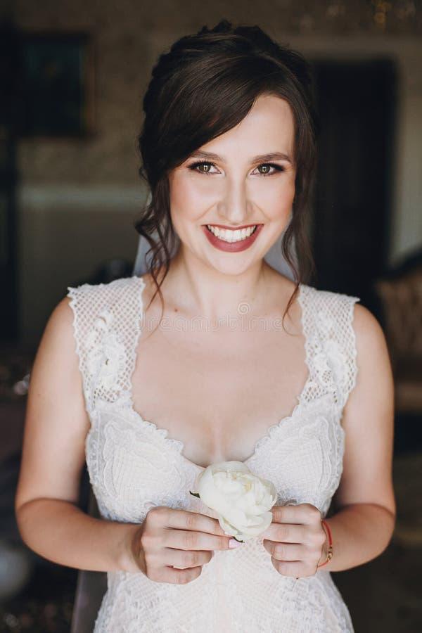Novia magnífica en el vestido que sorprende que sostiene el boutonniere blanco de la peonía en manos y que sonríe, para novio que fotos de archivo