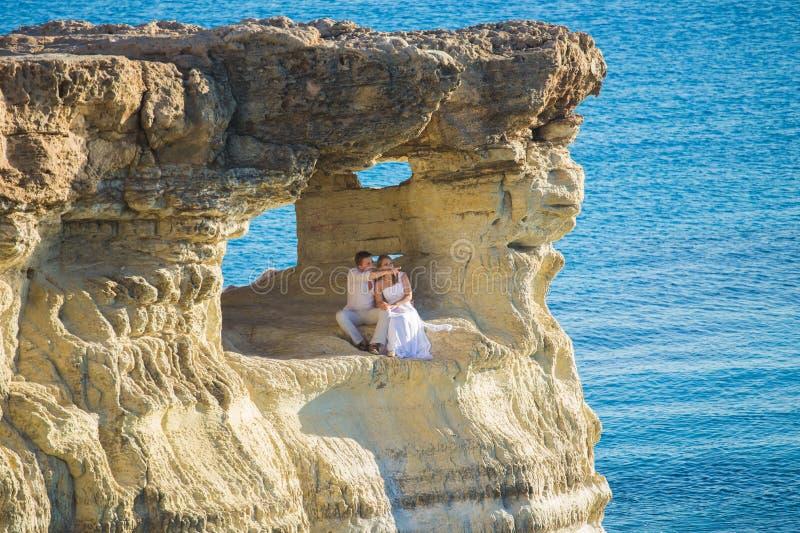 Novia magnífica hermosa y novio elegante en rocas, en el fondo de un mar, ceremonia de boda en Chipre fotografía de archivo