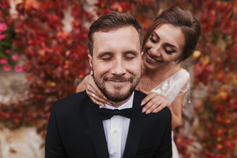 Novia magnífica que abraza suavemente al novio elegante en la pared vieja del autum imagenes de archivo