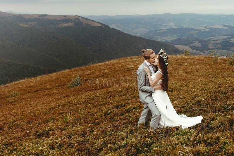Novia magnífica y novio elegante que abrazan, pares de la boda del boho, imagen de archivo