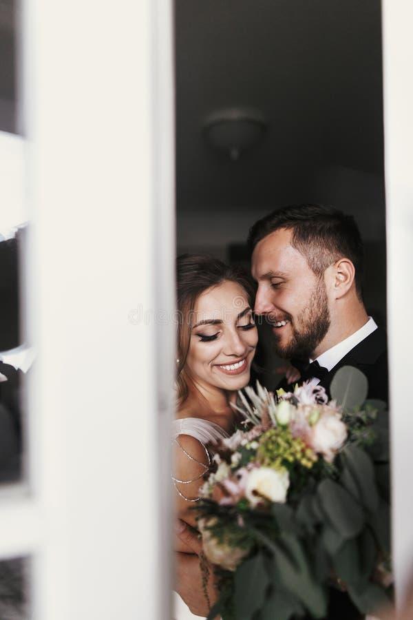 Novia magnífica y novio elegante que abrazan suavemente en la ventana Feliz imagen de archivo