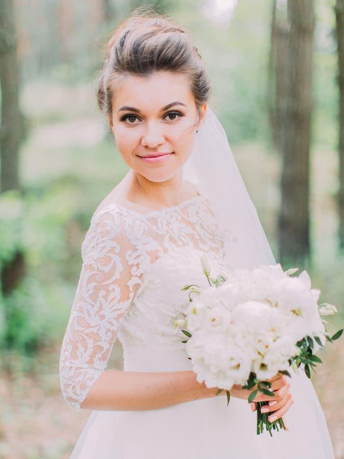 Novia maravillosa con el ramo de la boda que pasa tiempo en el retrato del retrato de medio cuerpo del bosque fotografía de archivo