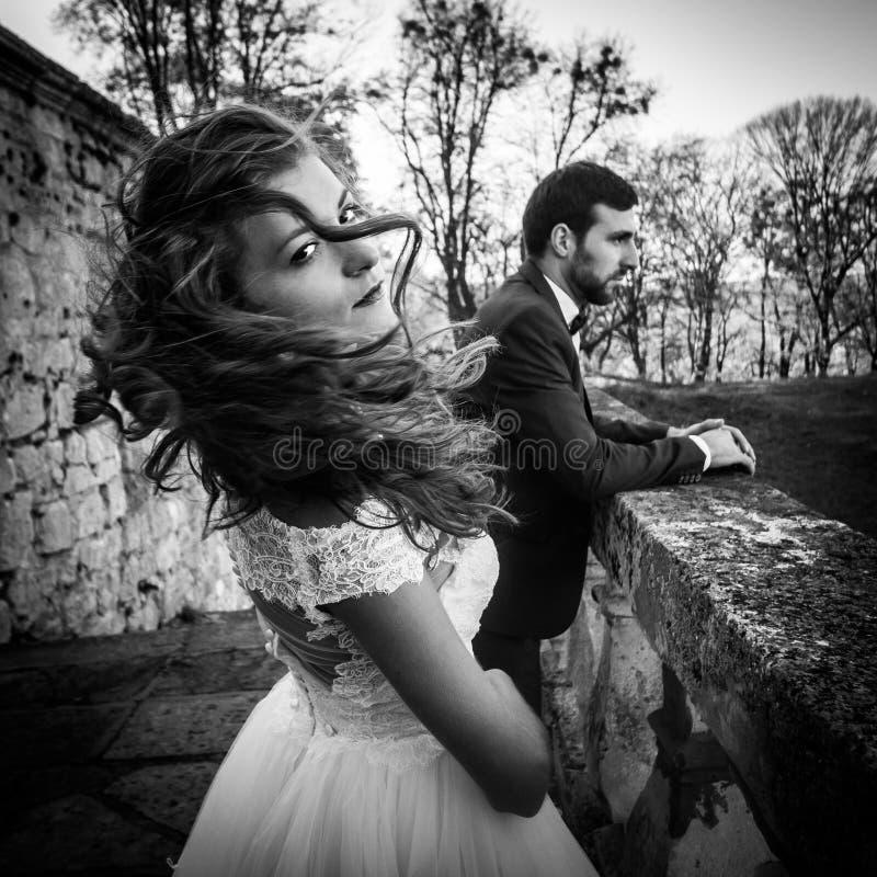Novia morena atractiva hermosa que agita su pelo cerca de su marido y pared vieja del castillo fotografía de archivo libre de regalías