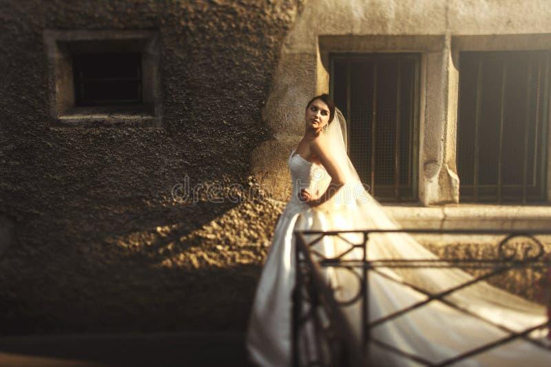 Novia morena hermosa en el vestido blanco que presenta cerca de la pared vieja en imagenes de archivo