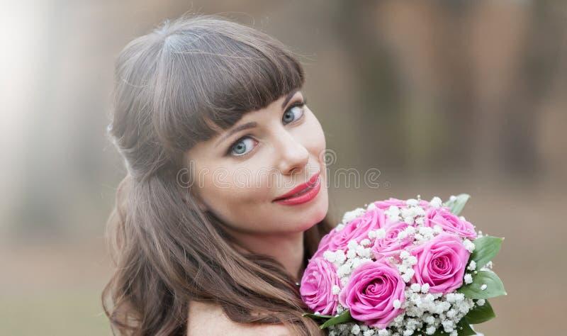 Novia morena, ramo de las rosas, sonrisa, cierre para arriba imagen de archivo libre de regalías