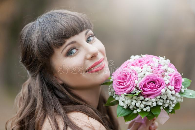 Novia morena, ramo de las rosas, sonrisa, cierre para arriba imagenes de archivo