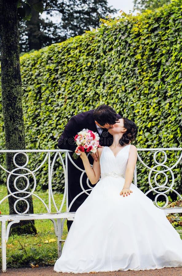 Novia muy hermosa con el novio que abraza y que baila en el parque verde, concepto real de la gente de la forma de vida imágenes de archivo libres de regalías