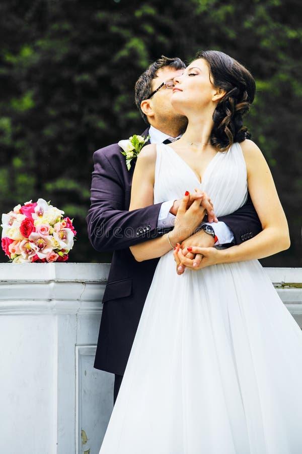 Novia muy hermosa con el novio que abraza y que baila en el parque verde, concepto real de la gente de la forma de vida foto de archivo