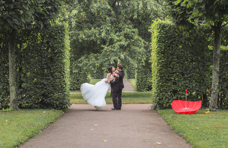 Novia muy hermosa con el novio que abraza y que baila en el parque verde, sonrisa feliz real de los pares de la boda junto para s fotografía de archivo