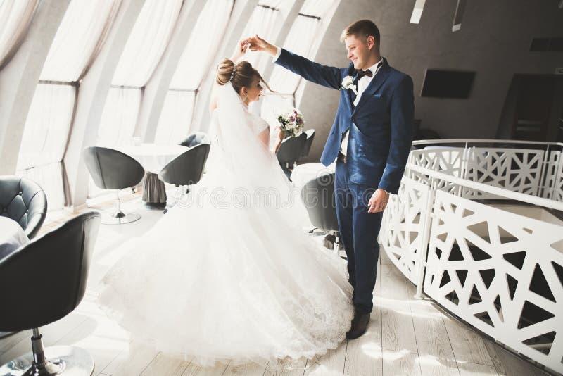 Novia perfecta de los pares, novio que presenta y que se besa en su día de boda foto de archivo libre de regalías