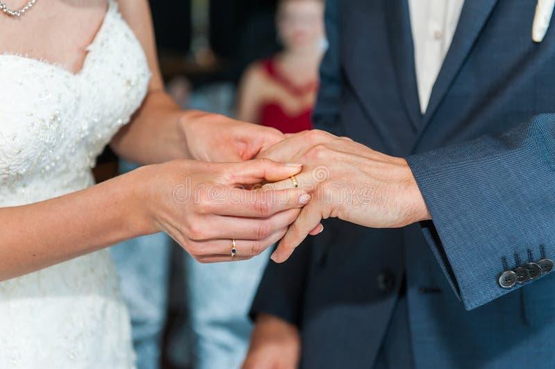 Novia puesta en el anillo de bodas en el finger de los novios fotos de archivo libres de regalías