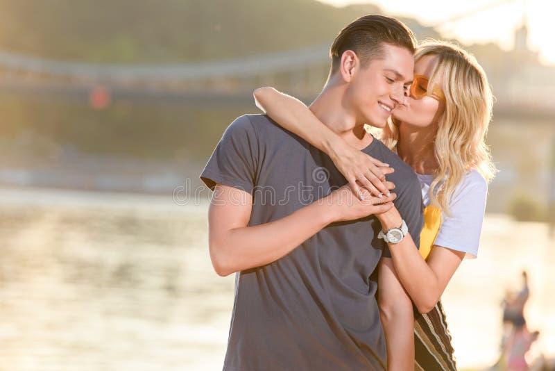 novia que abraza y que besa al novio en la playa del río fotos de archivo