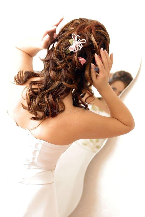 Novia que ajusta el pelo en espejo fotos de archivo