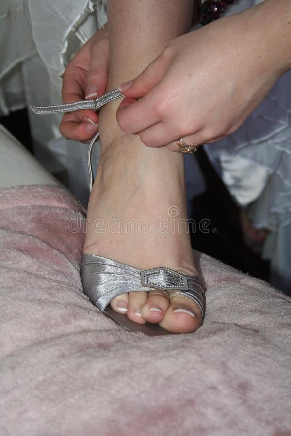 Novia que asiste a su zapato el día de boda imagenes de archivo