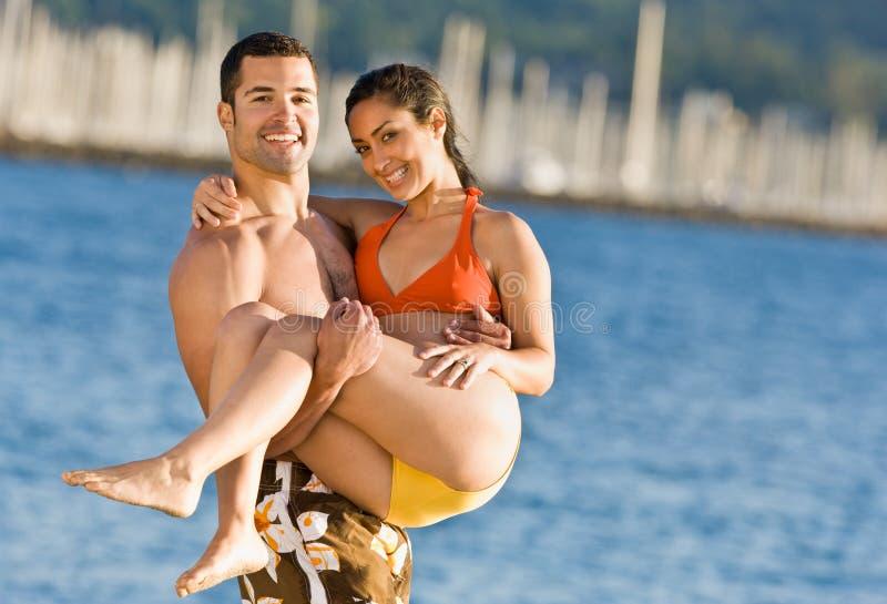 Novia que lleva del novio en la playa foto de archivo libre de regalías
