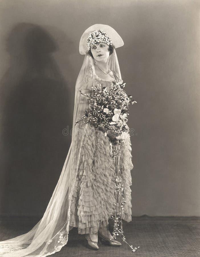 Novia que lleva el vestido de boda rizado y el tocado florecido imagenes de archivo