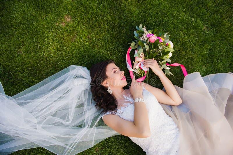 Novia que miente en la hierba con el ramo de la boda imagen de archivo