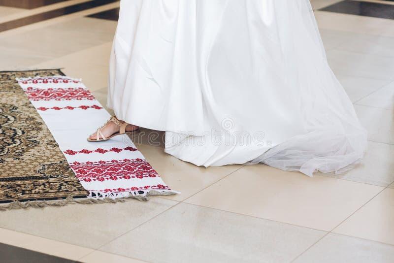Novia que pone la pierna en la toalla tradicional del bordado en duri de la iglesia imagenes de archivo