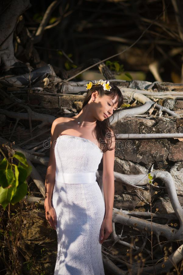 Novia que presenta en el medio de árboles tropicales en un fondo de la pared de piedra imágenes de archivo libres de regalías