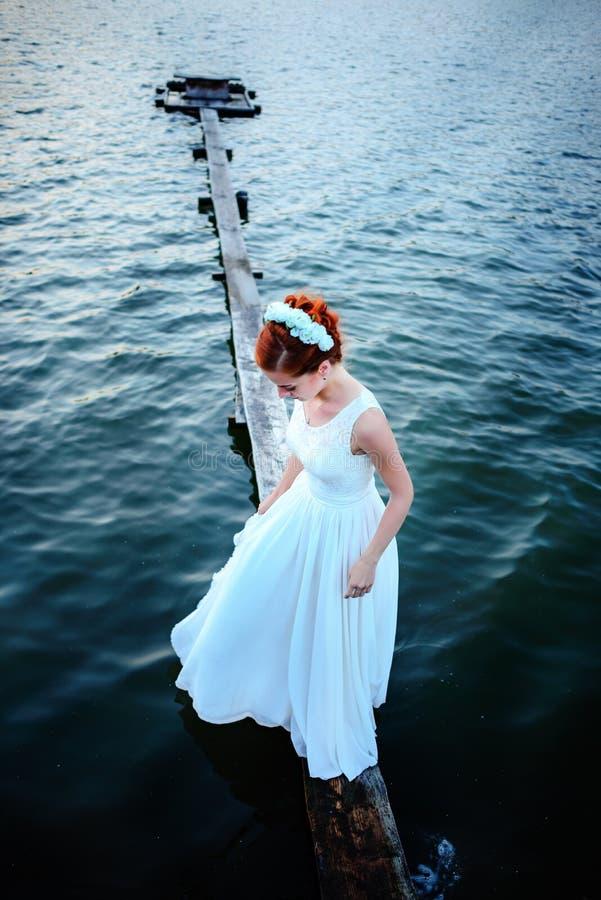 Novia que se coloca en el muelle cerca del agua en un vestido blanco imágenes de archivo libres de regalías
