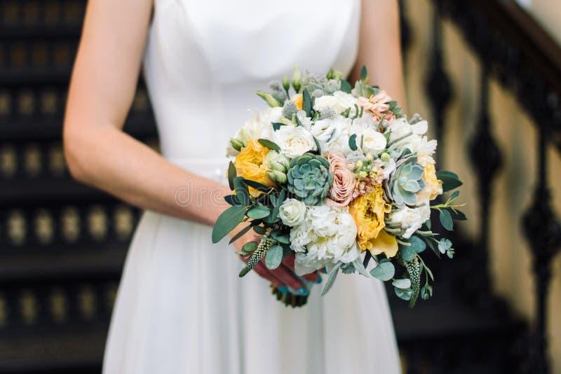 Novia que sostiene el ramo de la boda, con las flores suculentas, primer foto de archivo libre de regalías
