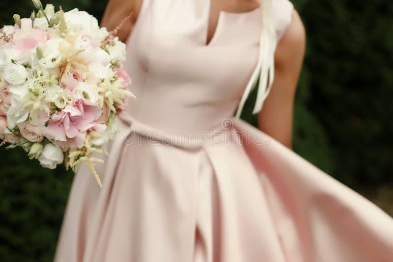 Novia que sostiene el ramo de la boda de flores rosadas y blancas en manos imagen de archivo libre de regalías