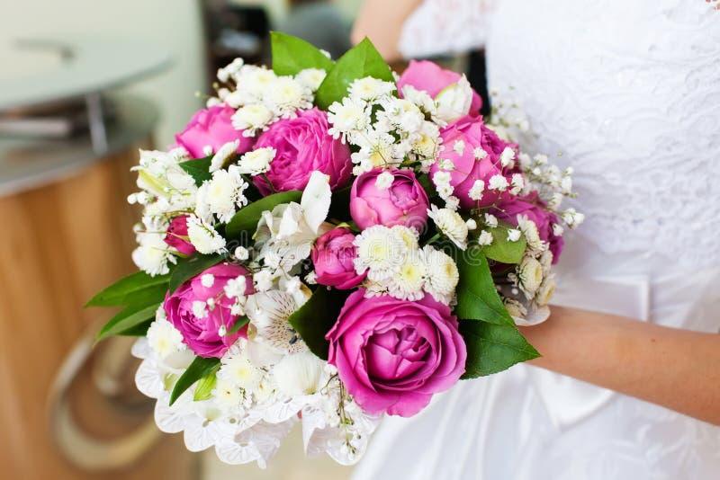 Novia que sostiene el ramo hermoso de la boda con las rosas rosadas imagenes de archivo