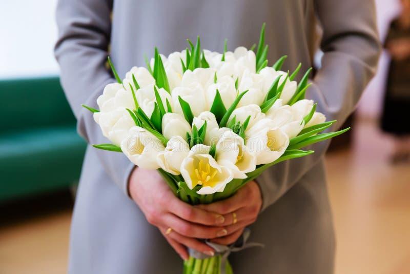 Novia que sostiene el ramo hermoso de la boda con los tulipanes blancos foto de archivo libre de regalías