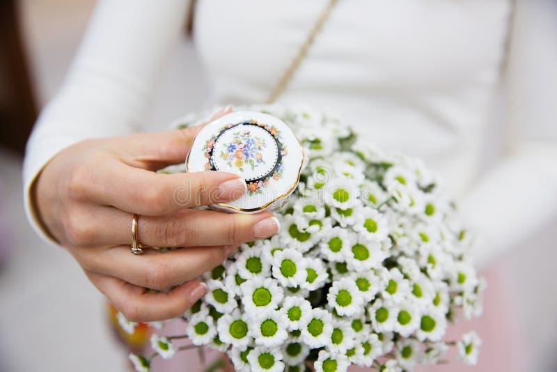 Novia que sostiene la caja para los anillos de bodas y el ramo imagen de archivo