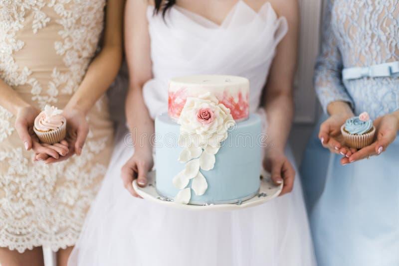 Novia que sostiene un pastel de bodas hermoso fotografía de archivo